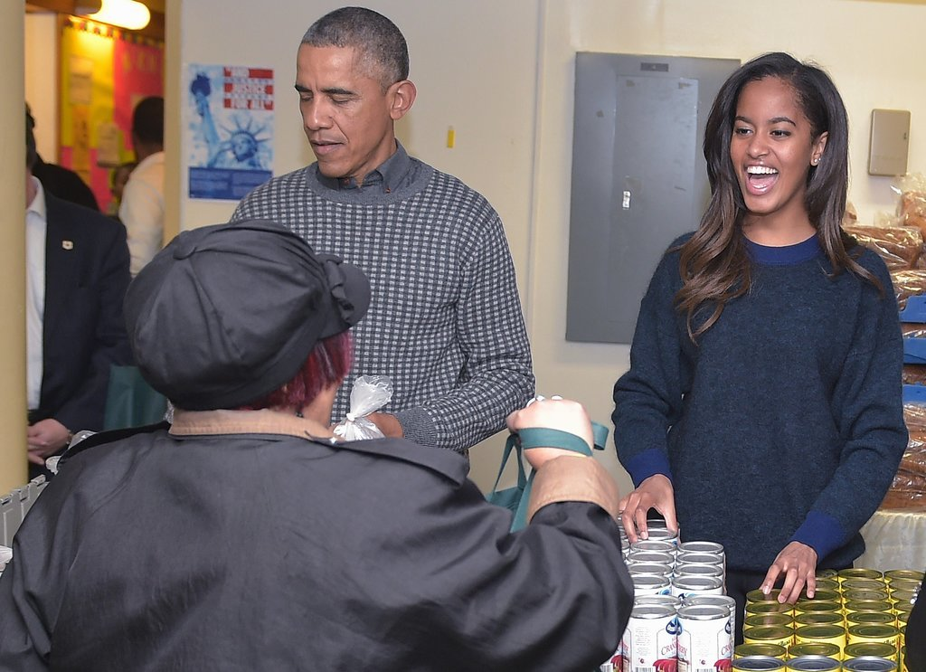 Malia smiled alongside her dad while distributing food at a Bread For the City event in November.