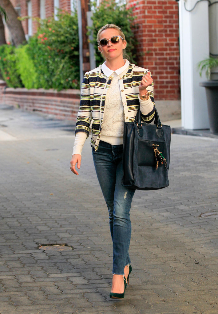 Reese toted her large Draper James bag, wearing distressed denim, a collared shirt, and a striped blazer.