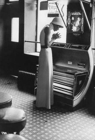 Circa 1972: At Harlem's Lucky Spot Restaurant wearing a Halston dress;byBerry Berenson