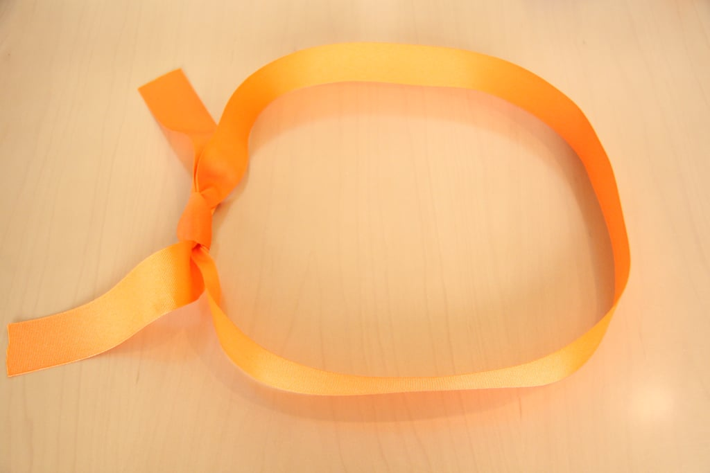 First, make a loop with the ribbon and tie a knot. You will start to place the folded diapers in the ring.