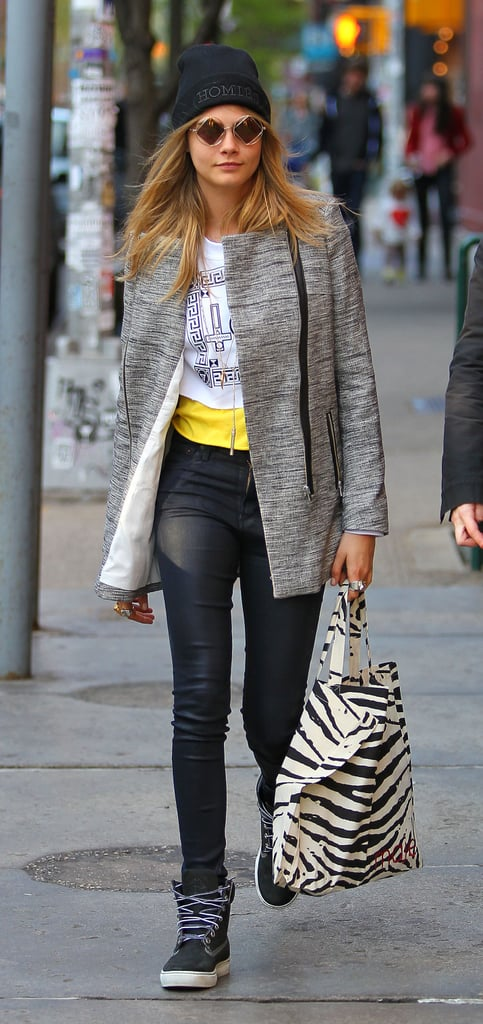 Cara Delevingne showed off her sporty side in NYC. She paired black leather Citizens of Humanity jeans with high-top sneakers, a tweed coat, a black beanie, geometric-print sunglasses, and zebra-print tote.