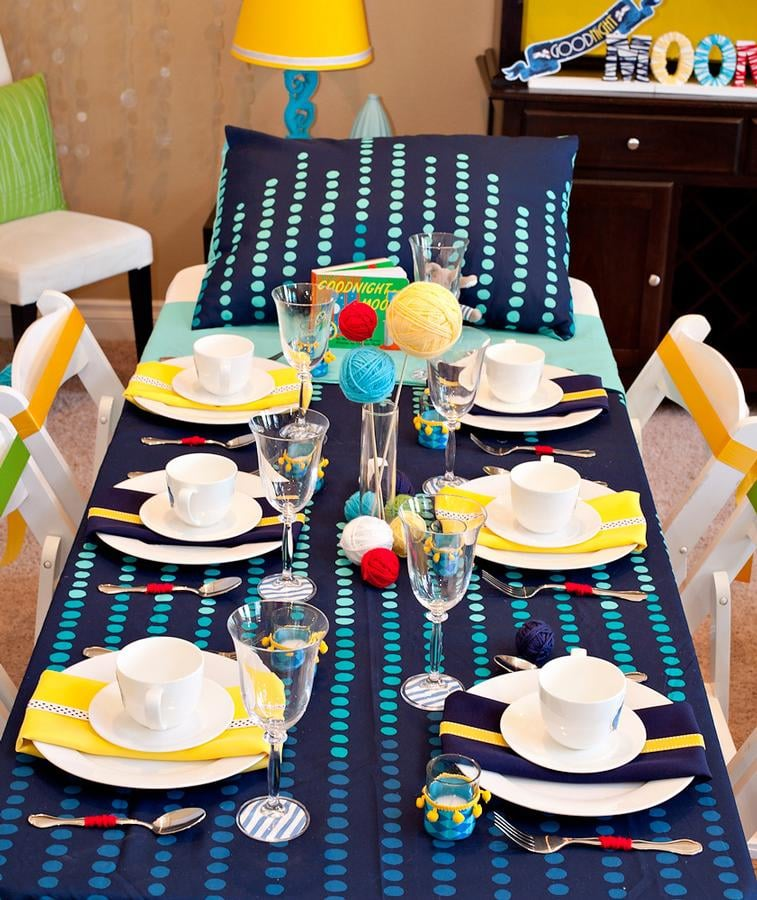 Colorful balls of yarn — which tie into the theme thanks to the cute kittens batting them around in the story — decorated the two party tables. Source: Hostess with the Mostess