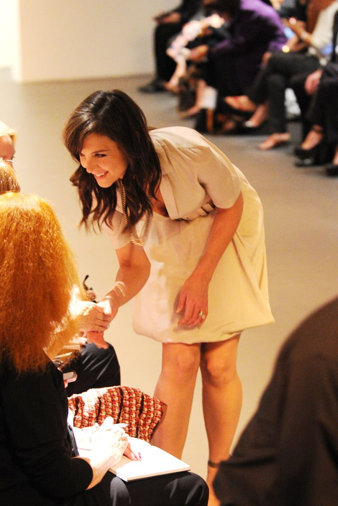 Katie Holmes chatted with friends while waiting for the Spring Calvin Klein show to start in September 2010.
