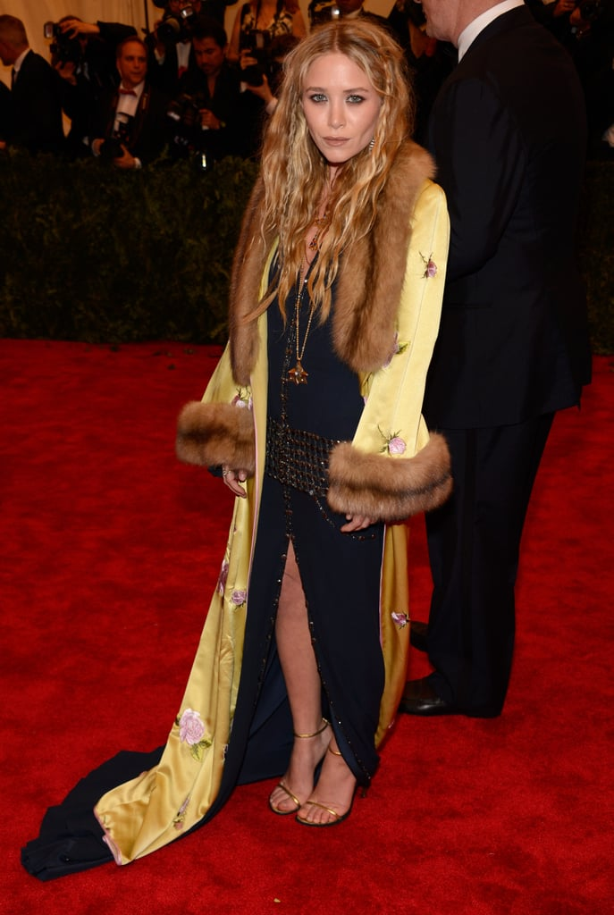 Mary-Kate Olsen layered up in a black studded slit-front Chanel dress and a yellow printed fur-collar coat.