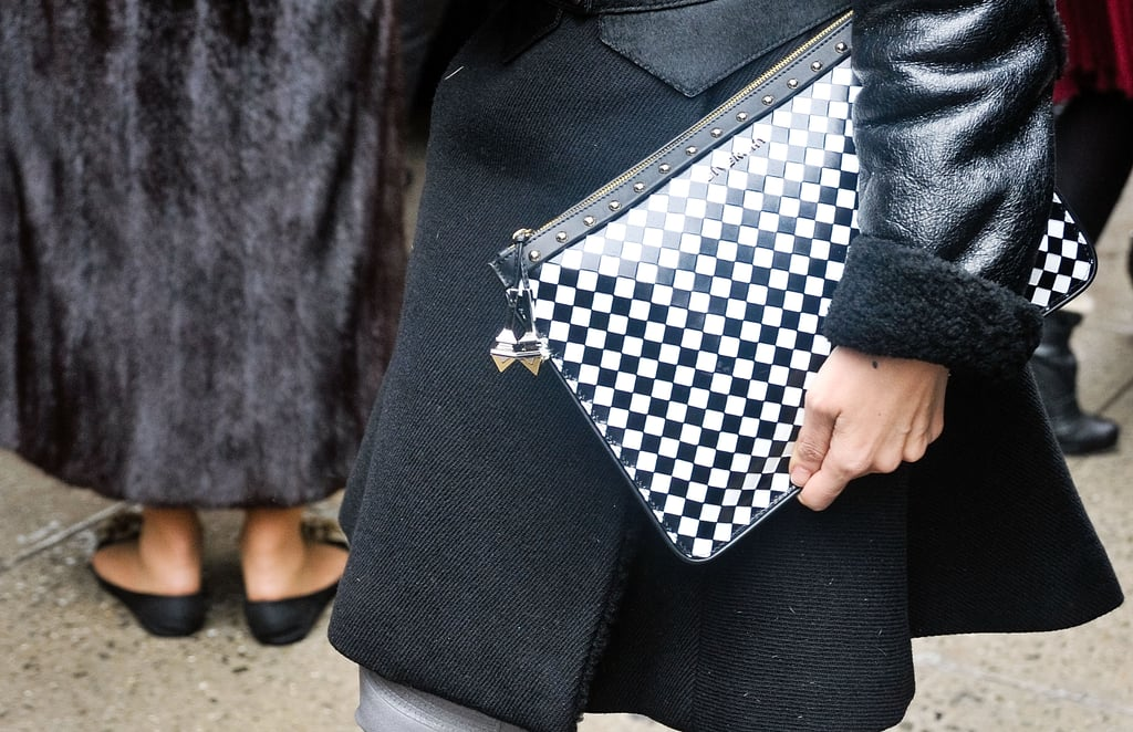 An eye-catching black-and-white checker-print clutch in a sleek silhouette.