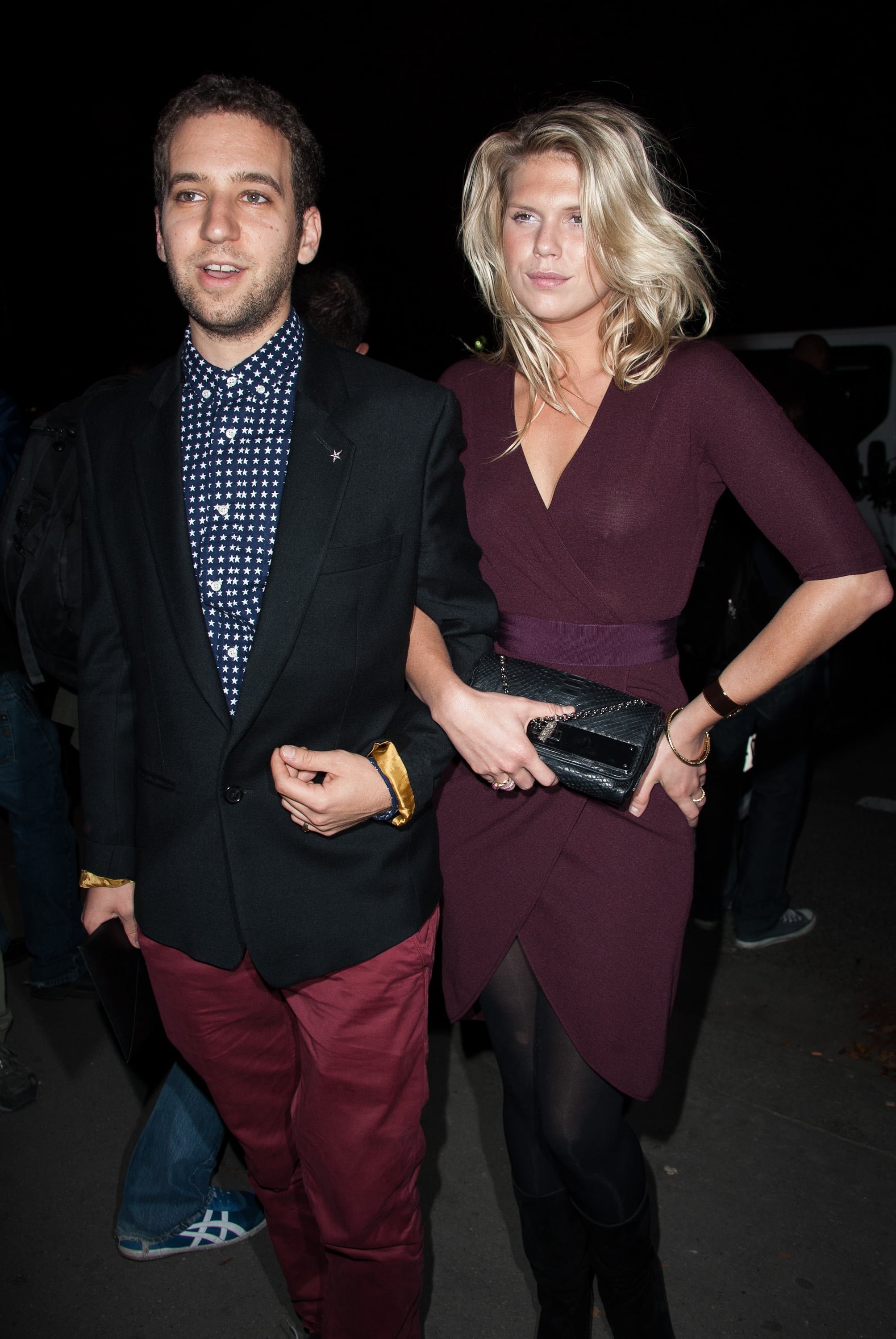 Alexandra Richards added black tights and a textured clutch to her burgundy-hued wrap dress at Saint Laurent.