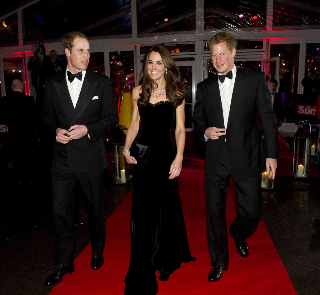 Kate Middleton hit the red carpet in a black velvet Alexander McQueen gown at the Sun Military Awards in London with husband Prince William and brother-in-law Prince Harry in tow.
