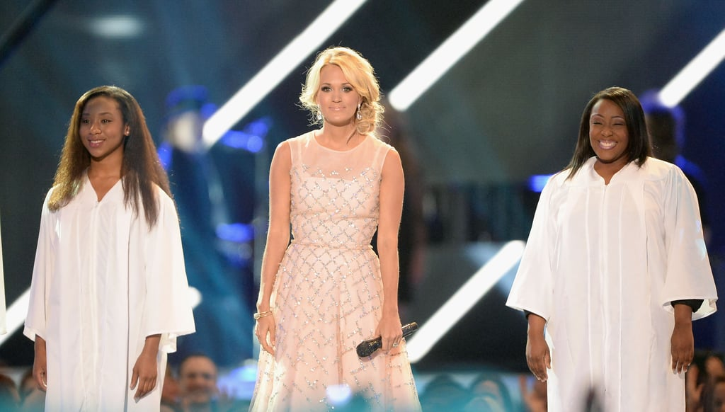Carrie Underwood stood on stage with choir members.