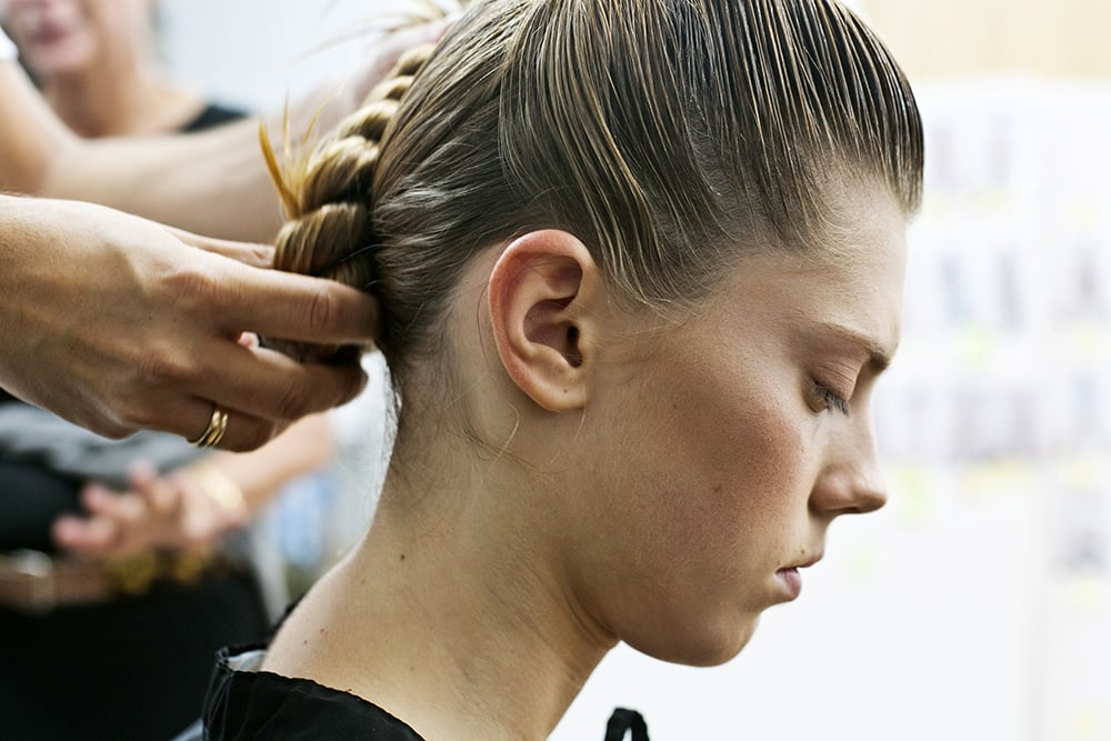 Finally, she curls the hair into a chignon, securing it with hair pins. To keep every hair in place, she secures with Kérastase Double Force Controle Ultime, an extra-hold hair spray.