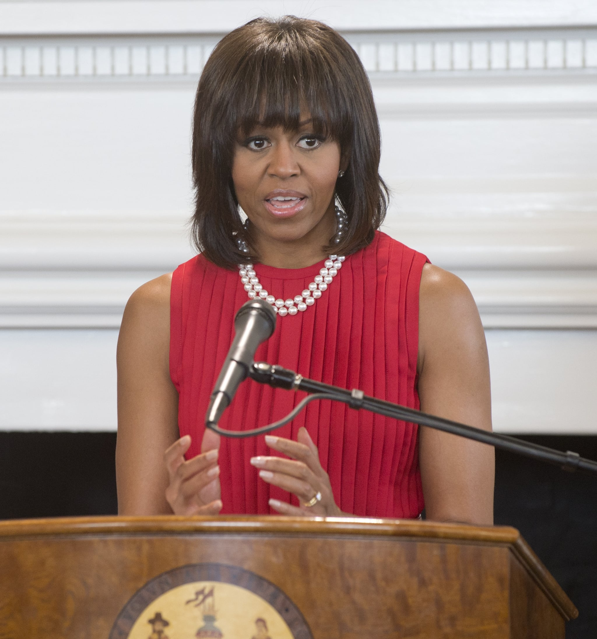 The crisp red pleats of her Michael Kors sheath provided the perfect color complement to her double strand of pearls.
