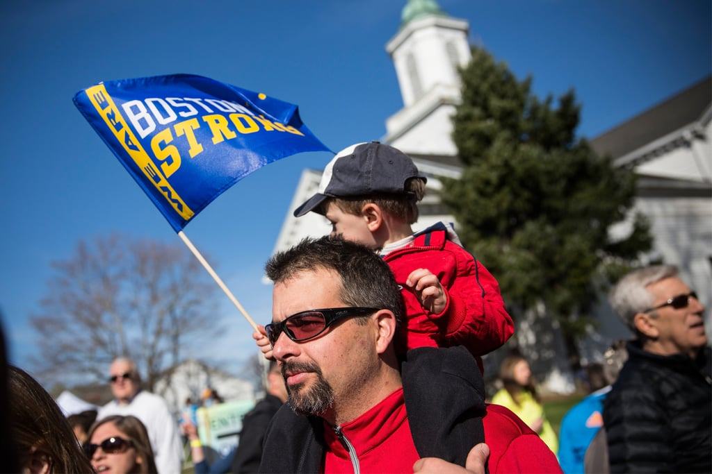 "A little boy sat on his father's shoulders holding a ""Boston strong"" flag."