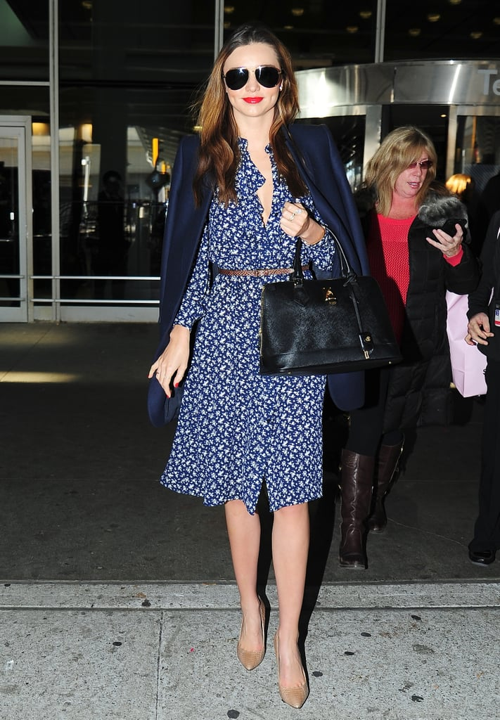 Miranda always inspires us to dress up when traveling. Here, she was true blue in a printed dress and solid blazer.