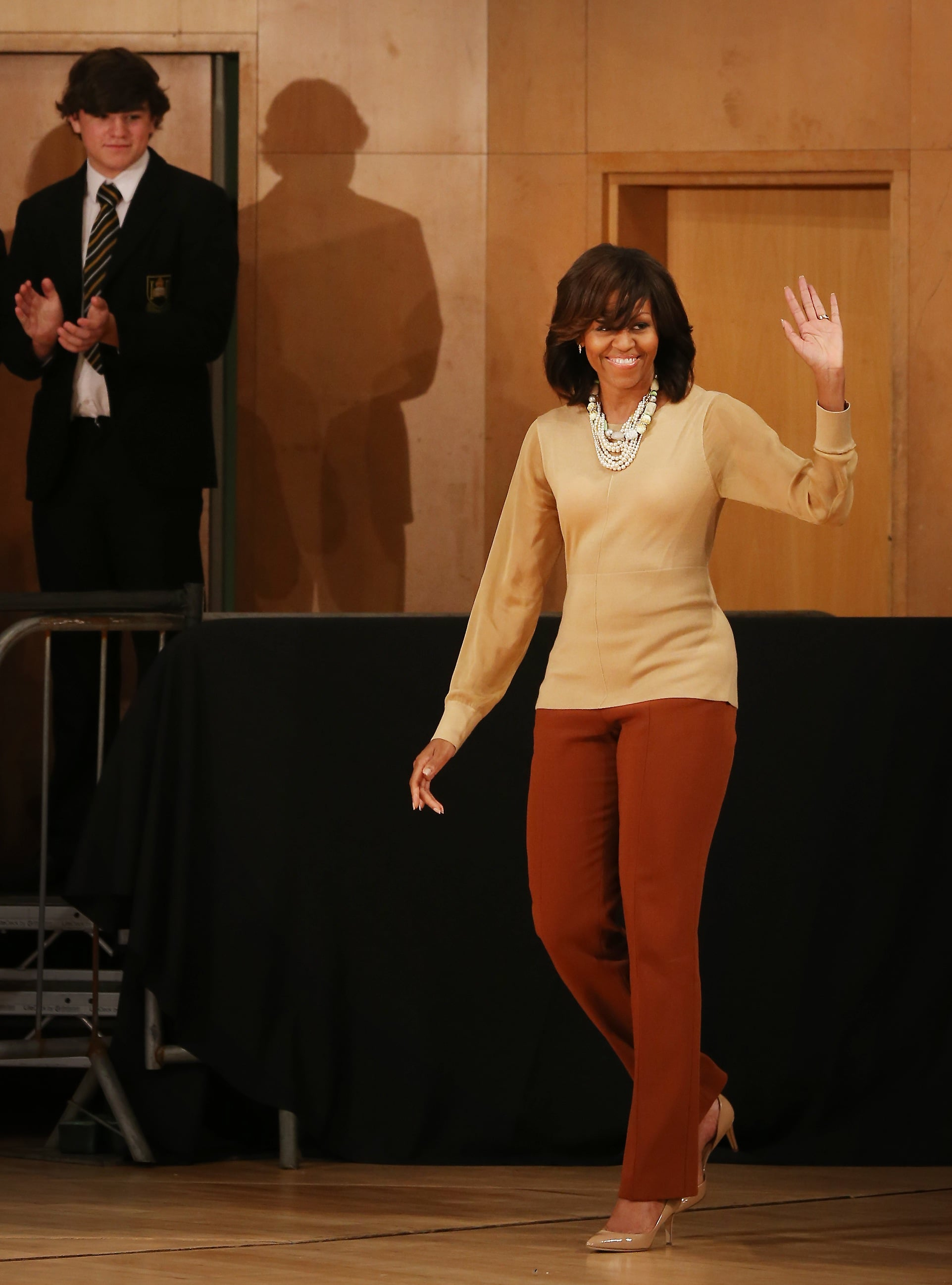 Inside, when Michelle took off her coat, she revealed an equally stylish ensemble: a nude sheer-sleeved blouse and rust-colored trousers, accessorized with a multistrand necklace and nude patent pumps.