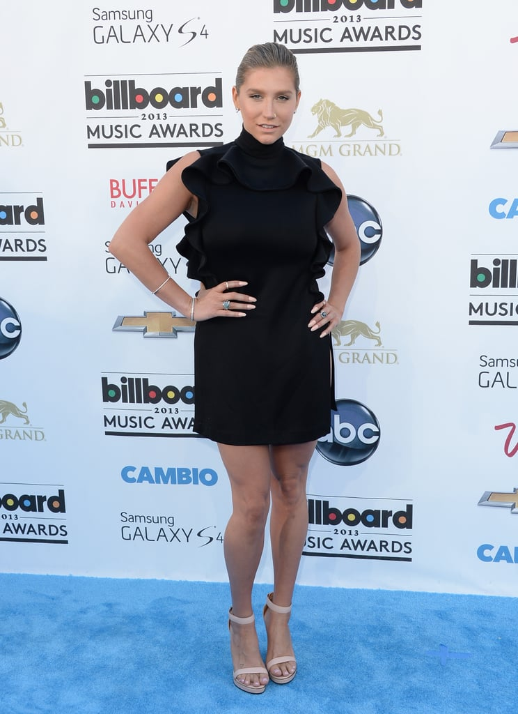 Ke$ha ditched her funky layers for an incredibly chic little black ruffle dress, minimalistic nude ankle-strap sandals, and Jupiter Jewelry diamond bracelets.