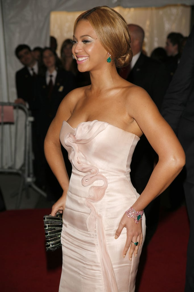 To finish her soft-hued look, Beyoncé accessorized with green jewels and a black clutch.