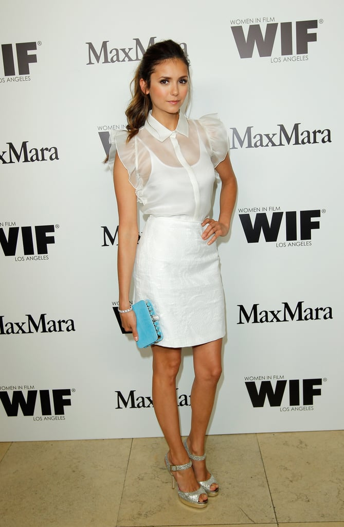 The sheer ruffled sleeves of this white cocktail dress are just the beginning of Nina's penchant for girlie flair. We also love her silver sandals and blue clutch.