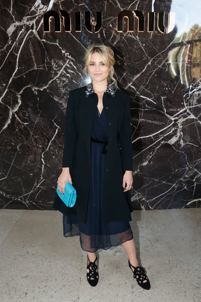 Before taking her front-row seat at Miu Miu, Dianna Agron covered up her ethereal navy dress with an jewel-collar coat, then added a turquoise leather clutch and a crystal headband, all by Miu Miu.