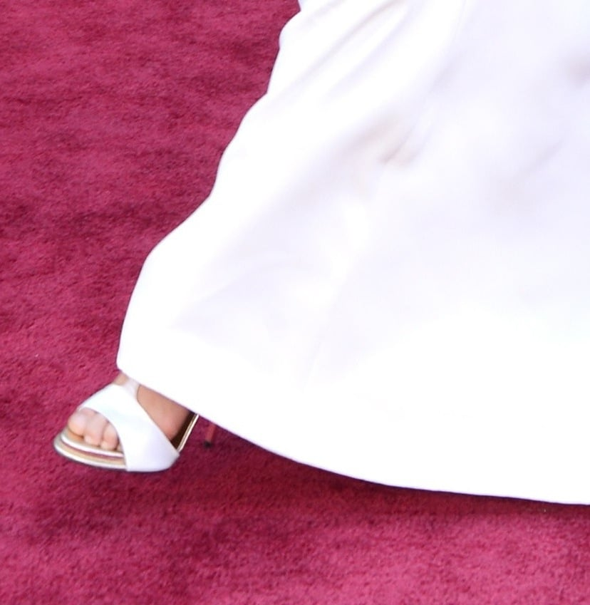 Charlize Theron coordinated her white Christian Dior Couture gown with equally fresh white T-strap sandals.