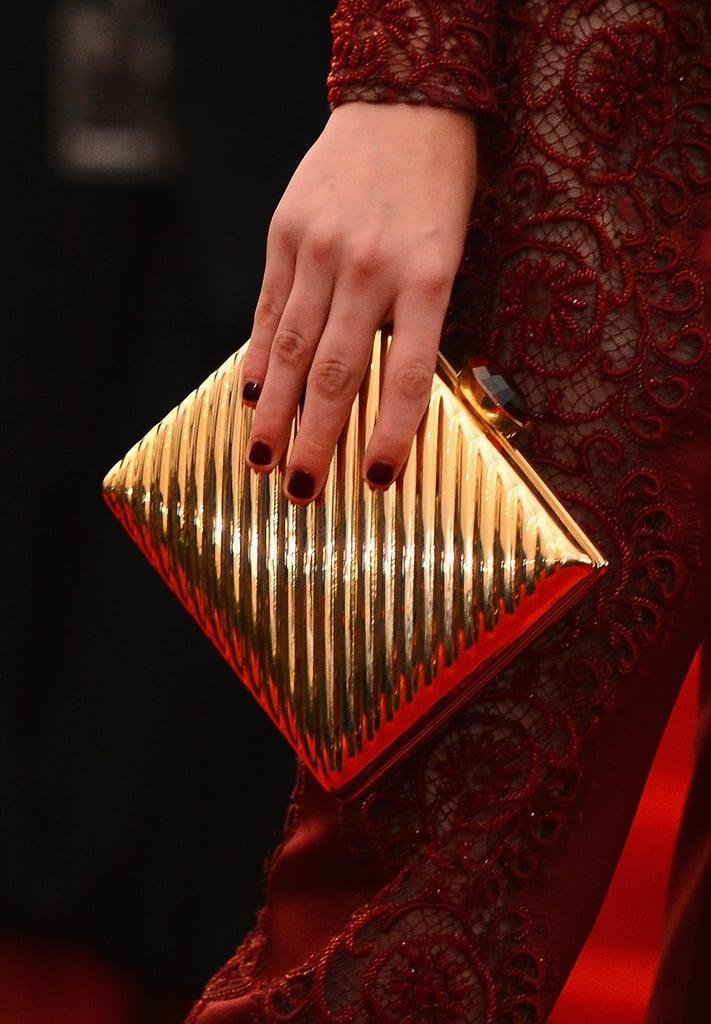 Kristen Stewart carried a gold box clutch alongside her Stella McCartney look.