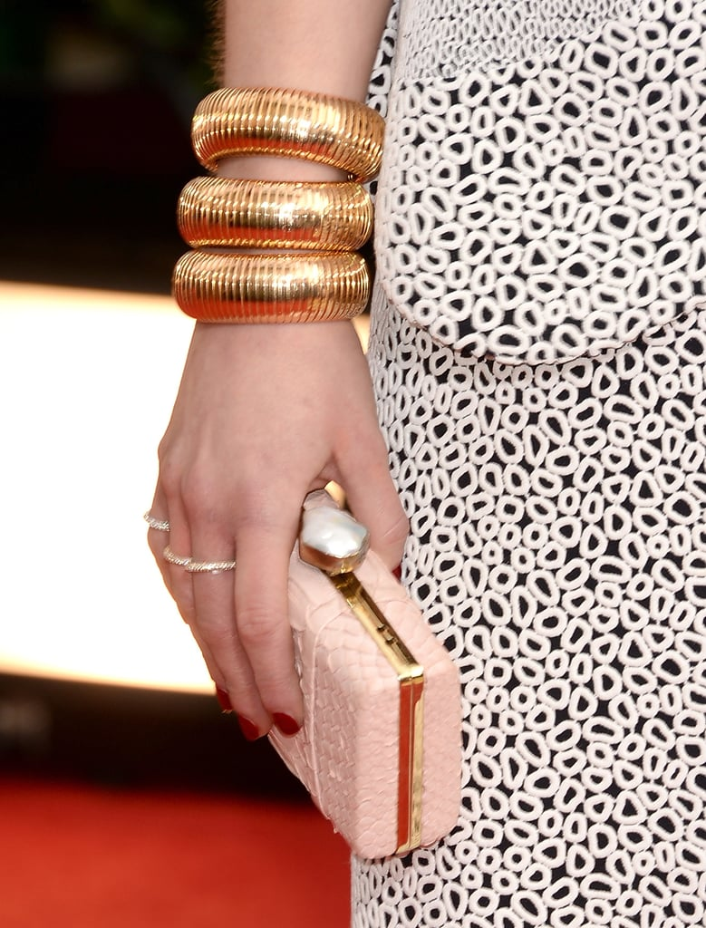 Emilia Clarke stacked a trio of thick Sidney Garber yellow gold bangles for added drama, then reached for a pale pink minaudière.