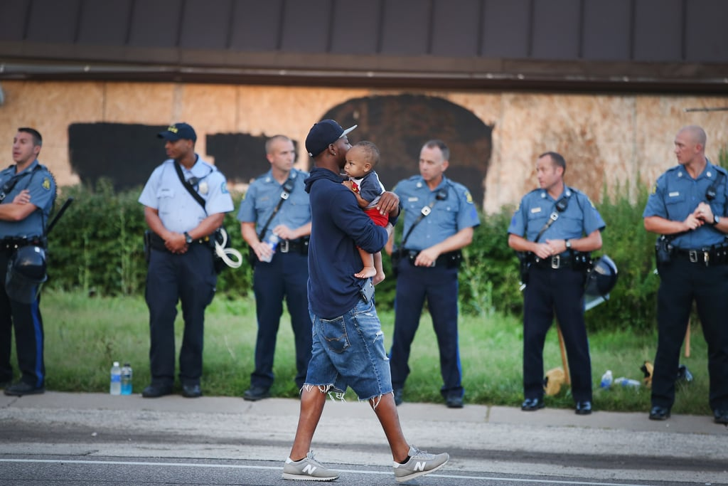 A man carried a baby past a line of police officers.