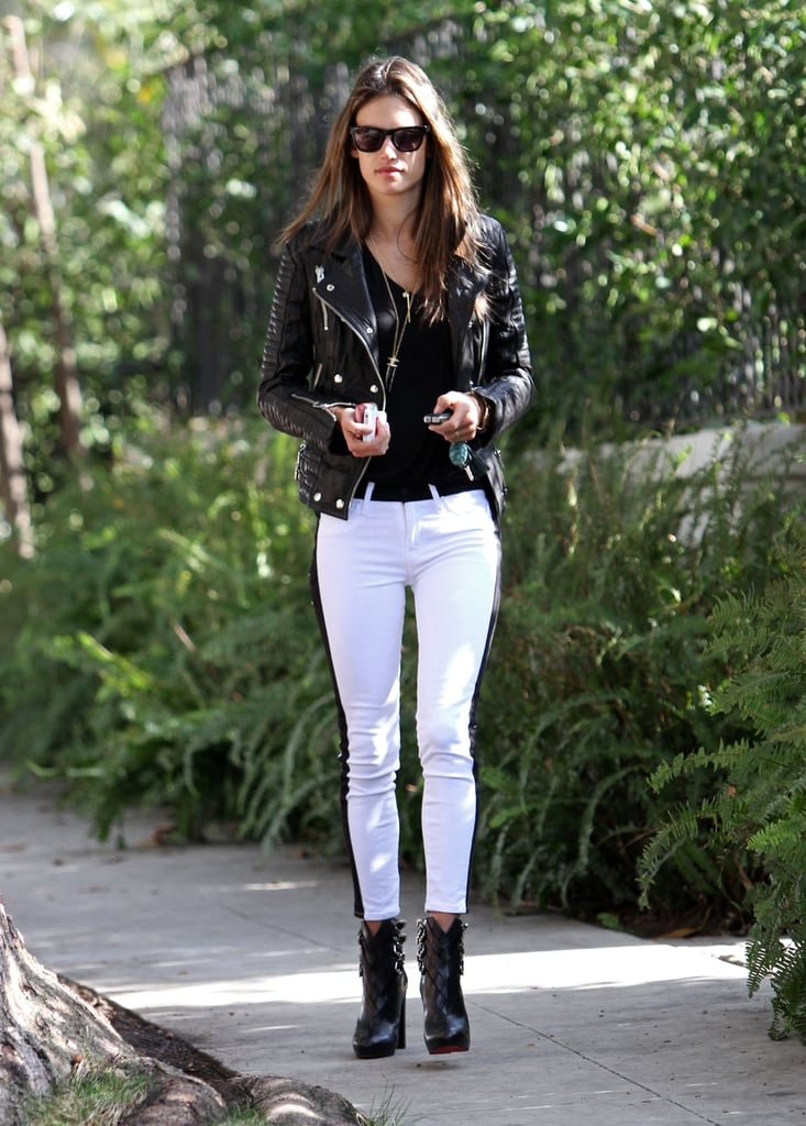Alessandra Ambrosio kept her colour palette black and white in Hudson tuxedo jeans, a black leather biker jacket, Christian Louboutin buckle booties, and Westward Leaning sunglasses during a stroll in LA.