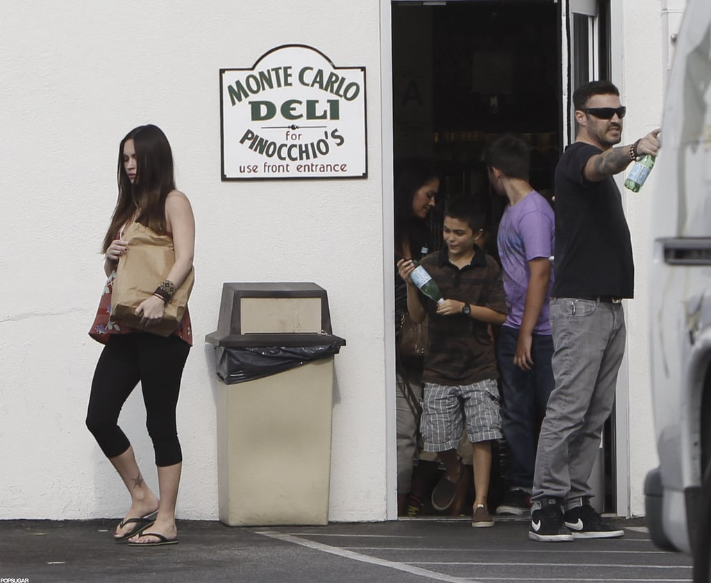 Megan Fox carried a brown bag out of a deli with husband Brian Austin Green and his son, Kassius.