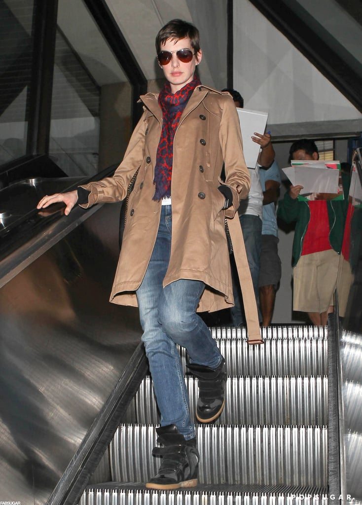 Anne Hathaway's travel style included black Isabel Marant sneakers, skinny jeans, and a dark camel trench coat.