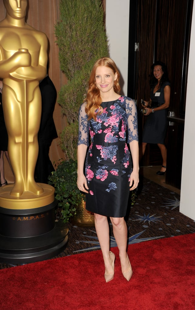 Jessica Chastain hit the red carpet in a navy-blue Erdem sheath, done up with lace sleeves and finished with powder-pink floral embroidery. She even echoed the soft pink shade with her lipstick.