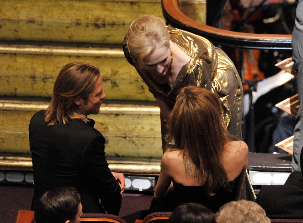 Meryl Streep stops to chat to Brad and Angelina in their seats at the Oscars.