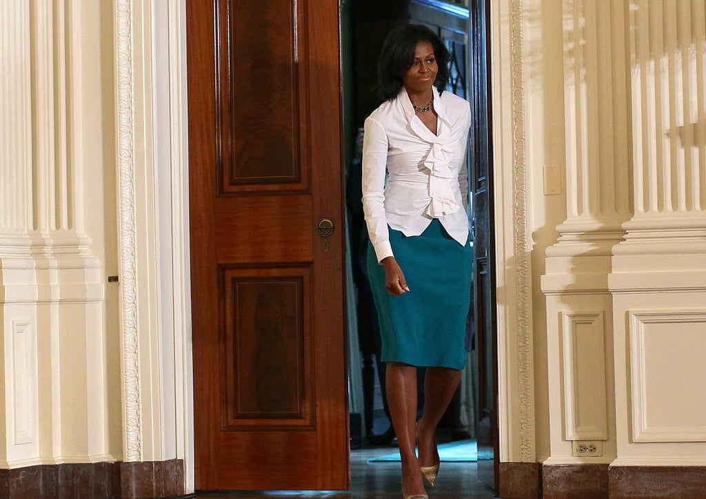 For a White House speaking event, Michelle chose a white ruched blouse with a teal skirt and nude pointy-toe pumps.