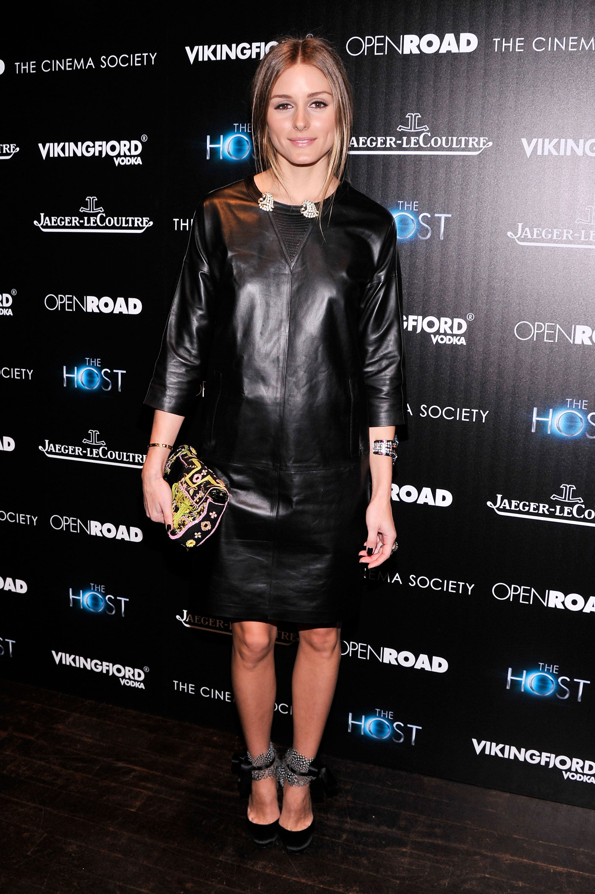 Olivia gave a minimalist leather sheath dress her signature accessory treatment with an embroidered clutch and a pair of feather-adorned heels.