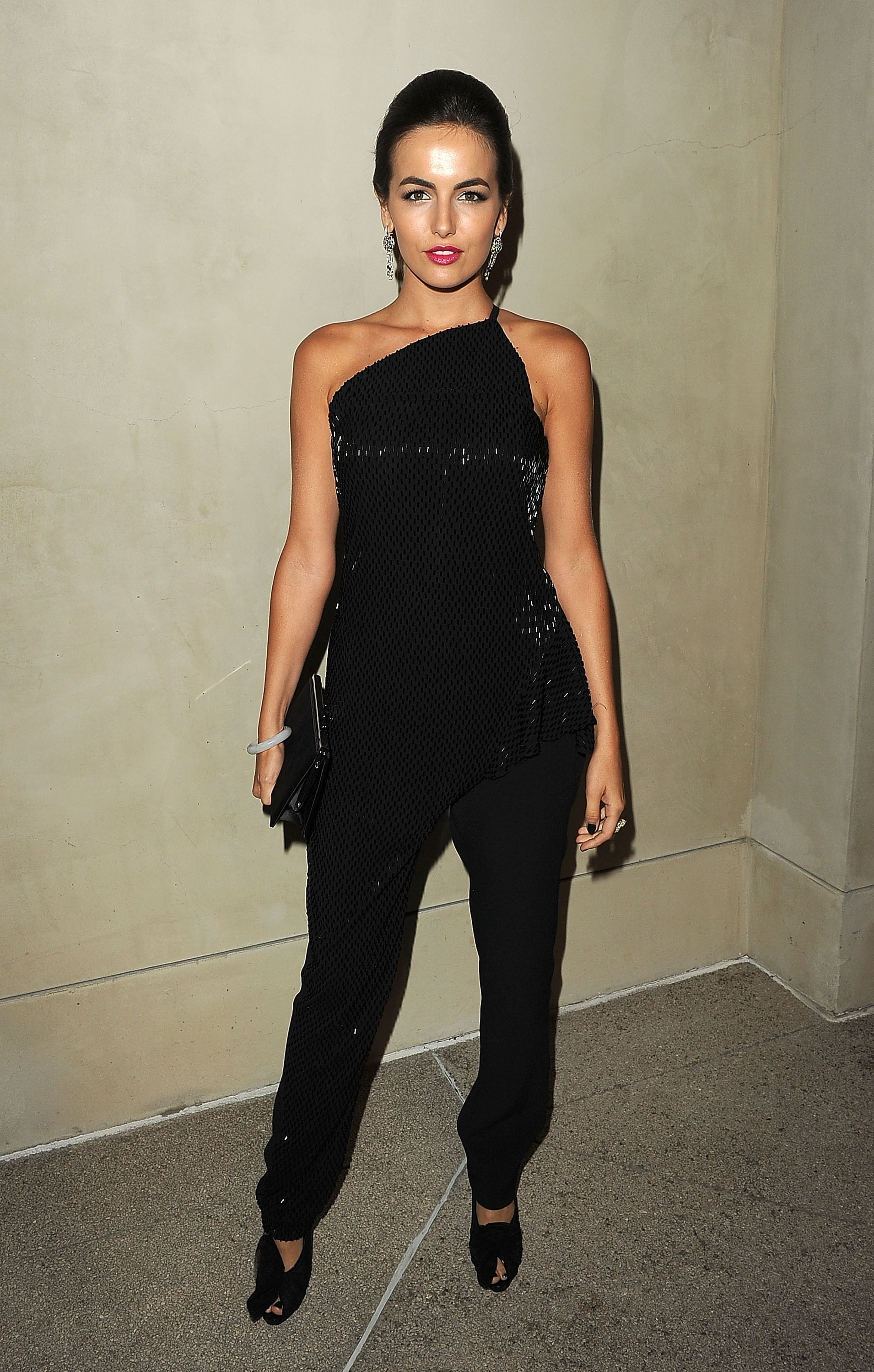 Camilla Belle in a black jumpsuit.
