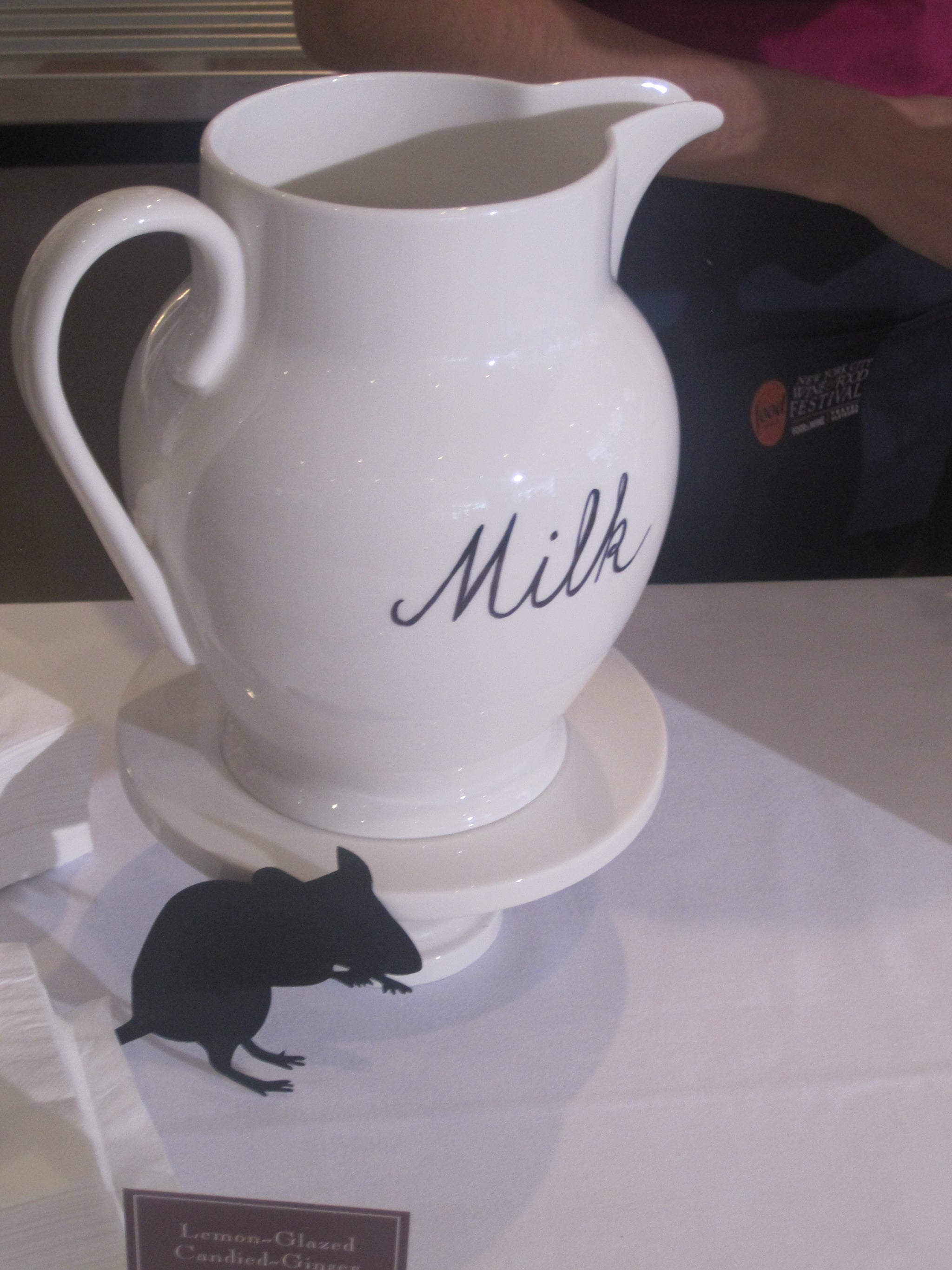 A rat poses by a milk pitcher.