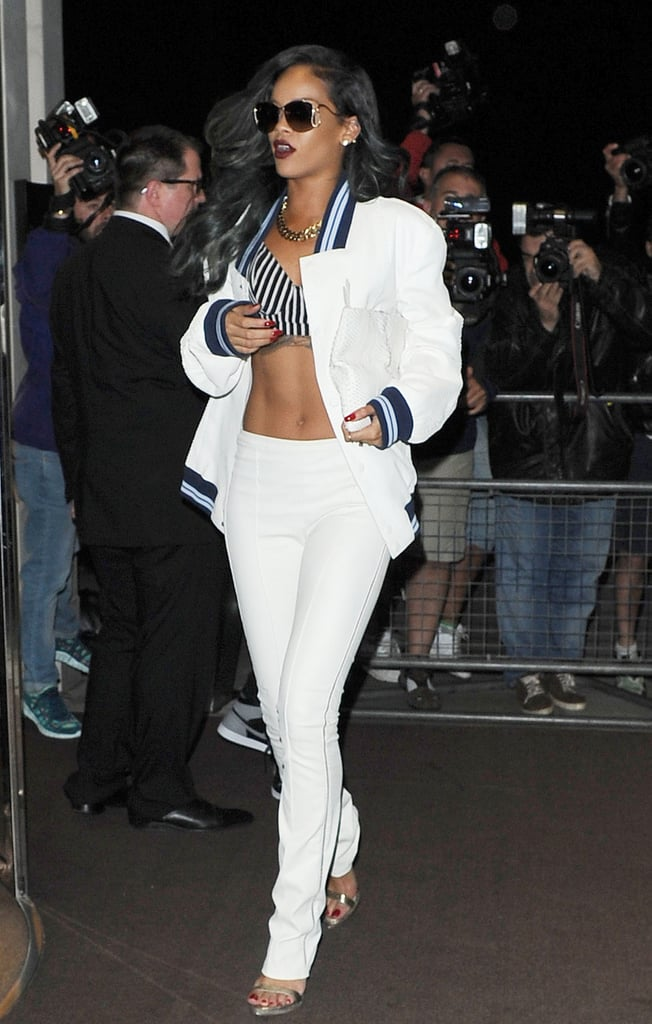 The singer wore a men's Roberto Cavalli white bomber jacket, coordinating pants, and a black-and-white bra top from her Rihanna for River Island collection while out at Cirque Du Soir in London earlier this year.
