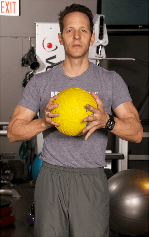 Start with your feet together and stand straight, holding a medicine ball chest-high between both hands.