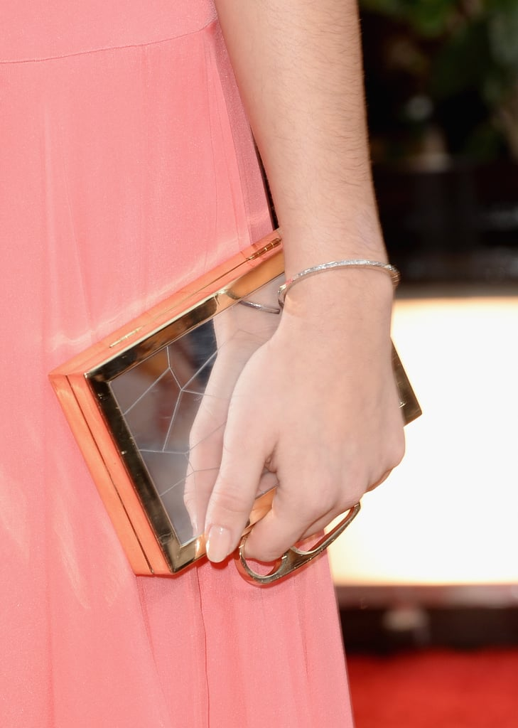 Sarah Hyland juxtaposed her soft pink gown with a gold box clutch.