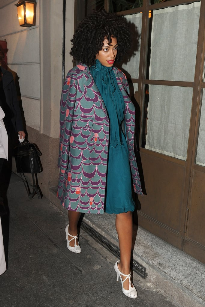 During Milan Fashion Week Fall 2012, Solange Knowles topped her teal neck-tie dress with a purple printed coat and white-hot t-strap perforated pumps.