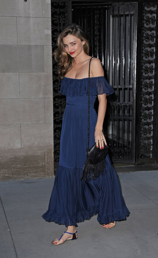 Miranda Kerr was feminine as ever in an off-the-shoulder navy maxi dress while out in NYC. She added a black fringe bag and blue t-strap sandals to her mix to complete her look.