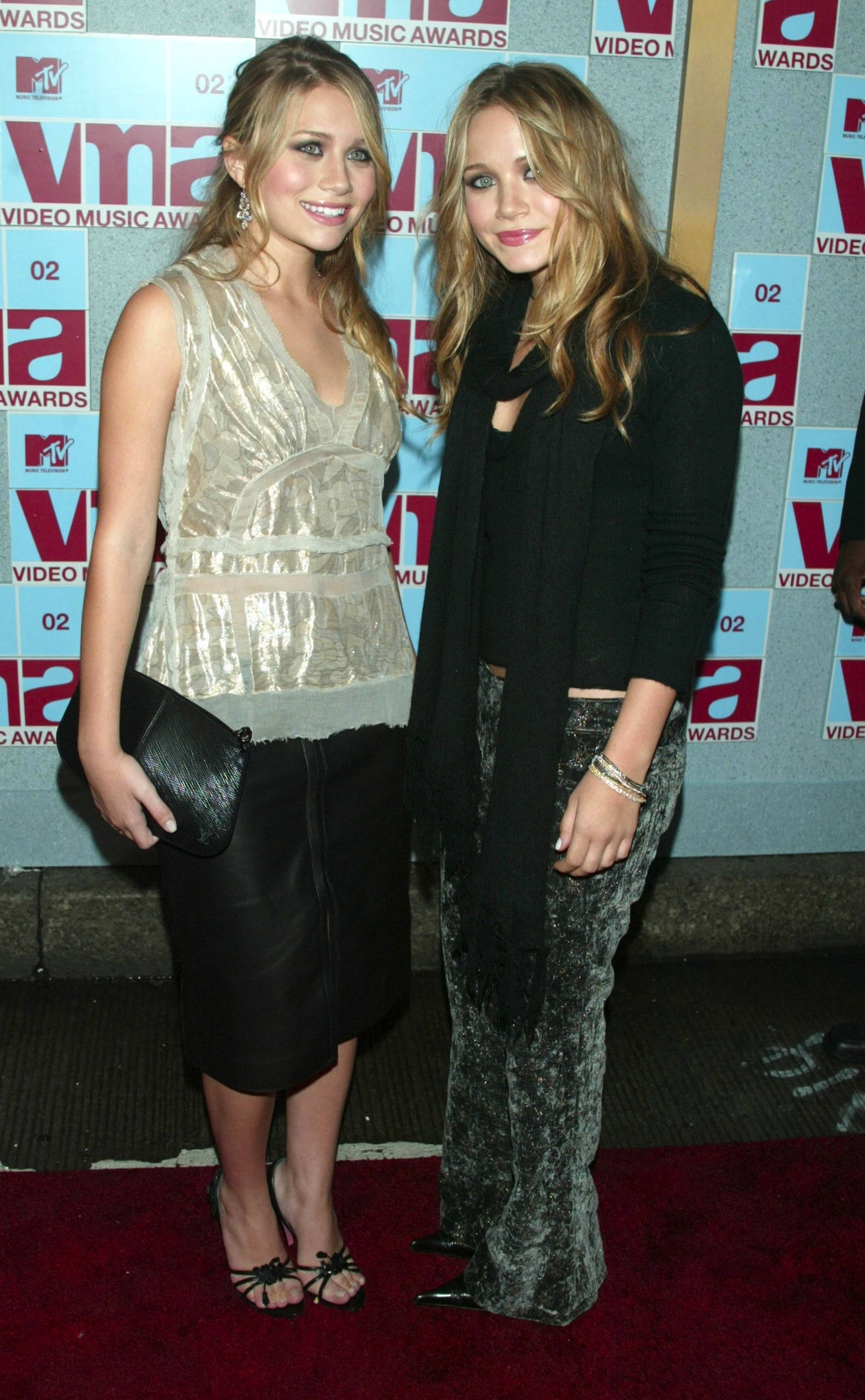 Twinning combo: At the 2002 MTV VMAs, the Olsens partied the night away in age-appropriate ensembles.  Ashley tempered her leather pencil skirt with an iridescent blouse and black sandals. Mary-Kate stood out in printed velour pants.