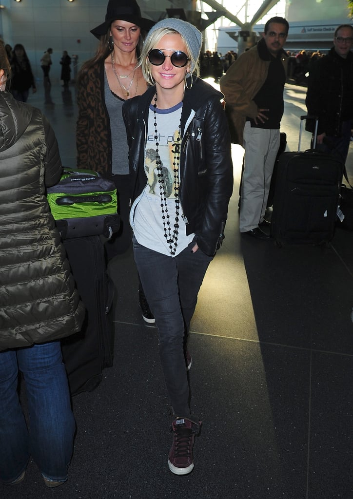 On another occasion while traveling, Ashlee Simpson paired her gray beanie with a quilted leather jacket, gray skinny jeans, high-top sneakers, and round sunglasses.