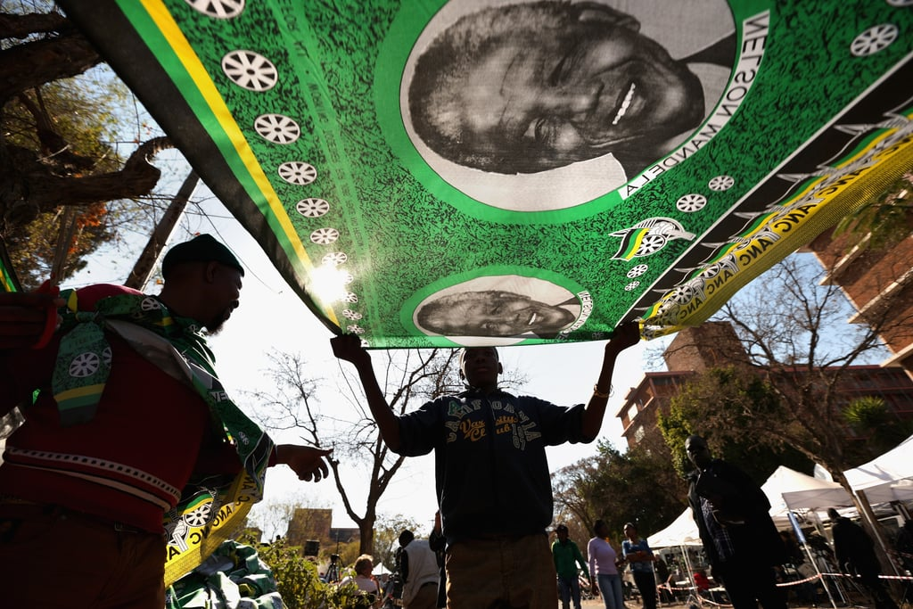 A man near the hospital held up a piece of fabric with Mandela's face on it to show his support.