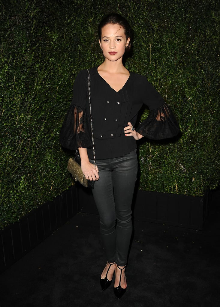 Alicia Vikander wore a black blouse from Chanel's Spring '13 collection, then paired it with slick, dark-gray jeans — casual but chic.