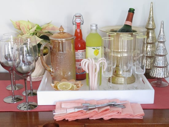 Here's an easy, elegant way to create your own makeshift home bar: begin with a black or white lacquer tray (this one is from West Elm is $24), then arrange everything (vintage stirrers, bar tools, Christmas decorations, wine glasses, napkins . . . you get the idea) with cocktail stirrers or bar foods. Impress guests with a brightly hued cocktail of Champagne, limoncello, and blood orange soda.