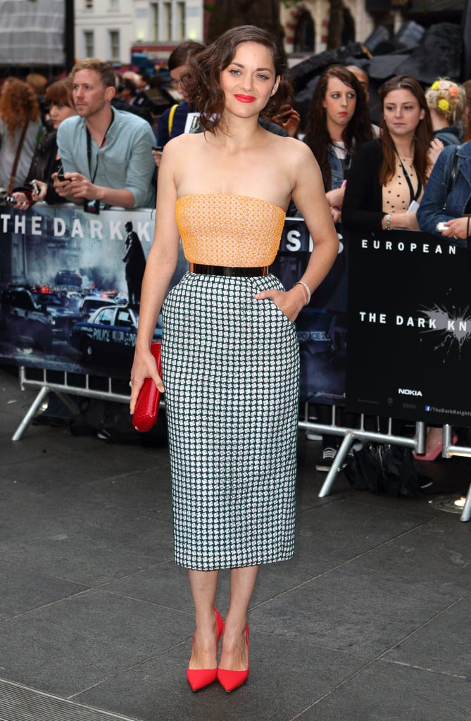 At the London premiere of The Dark Knight Rises, Marion Cotillard looked flawless in her Christian Dior Fall 2012 Couture mixed-print dress and bold red accessories.