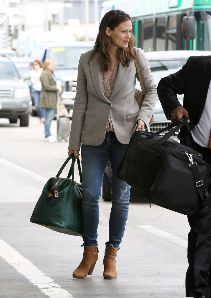 Jennifer Garner played it preppy when heading to catch her flight, mixing jeans with a blazer, ankle boots, and weekender bag.