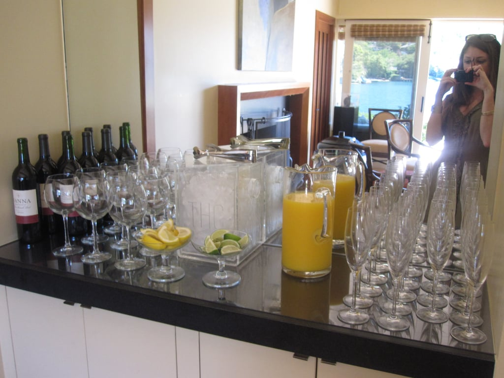 Red wine, fresh orange juice, and citrus wedges were on another bar.