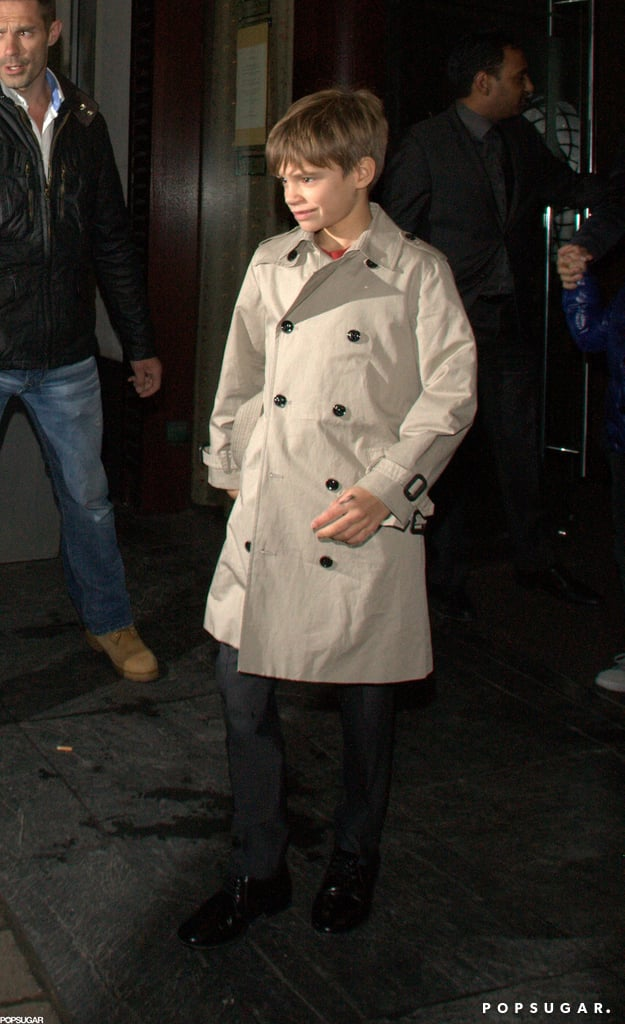 Romeo Beckham looked adorable in a beige trench coat Friday in London.