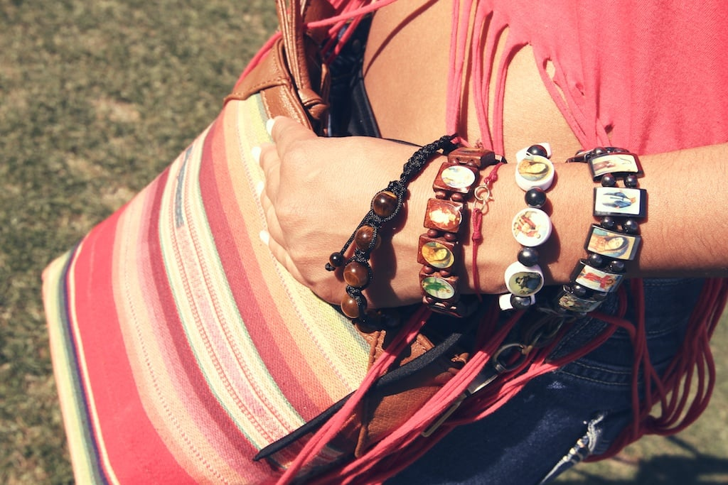 Artistic faith bracelets get paired up with a striped cross-body bag.