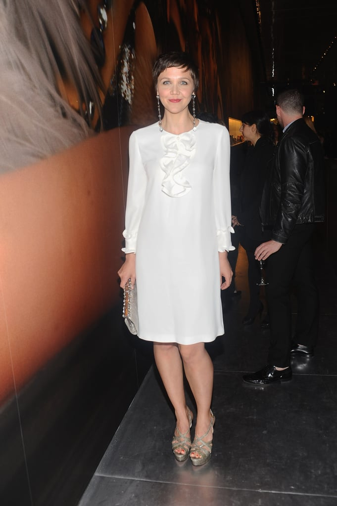 Maggie Gyllenhaal looked '20s chic in a Prada ensemble comprised of a white silk ruffle dress, gray crystal drop earrings, python multistrap platform heels, and black-and-white watersnake frame clutch at the  Prada and The Great Gatsby soiree celebrating the opening of a special Dress Gatsby exhibition.